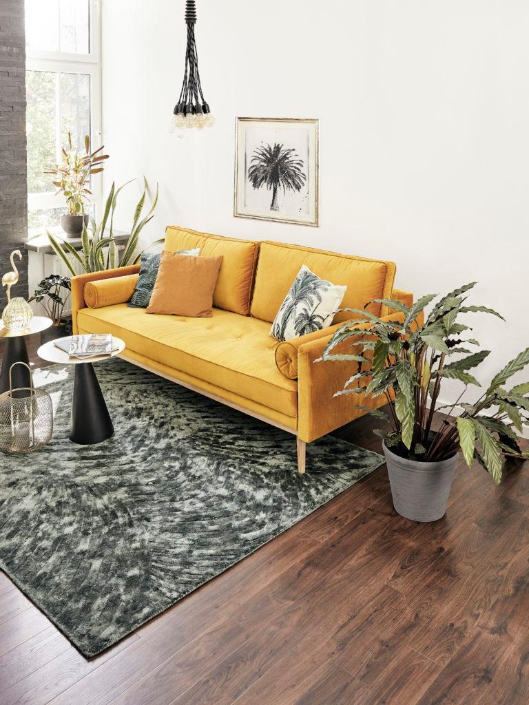 Salon z żółtą kanapą, stolikiem, roślinami oraz zdjęciem