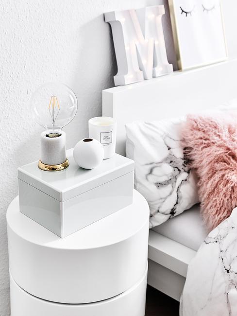 Biała sypialnia ze stolikiem nocnym, świecami oraz kocem