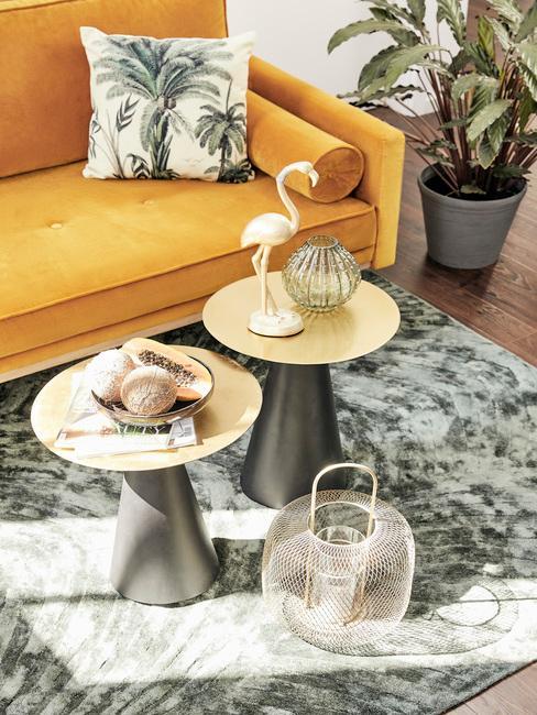 Zbliżenie na dwa stoliczki kawowe w salonie o zielonym dywanie oraz pomarańczowej sofie