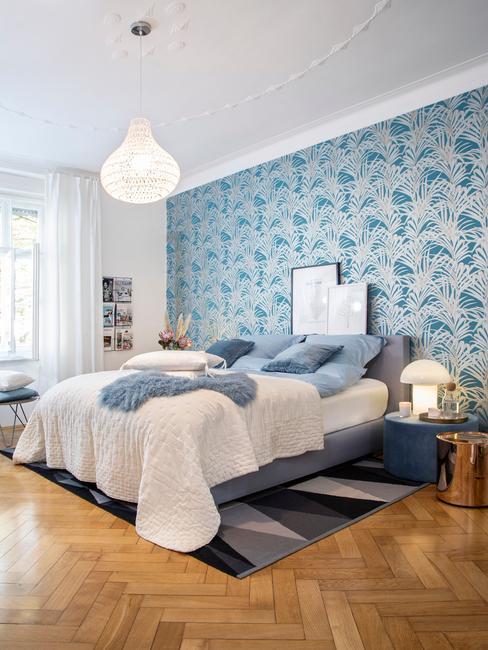 Sypialnia z szarym łóżkiem oraz biało - turkusową tapetą na ścianie
