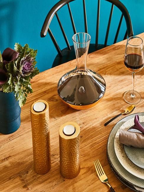 Jadalnia z drewnianym stołem, akcesoriami oraz turkusową ścianą
