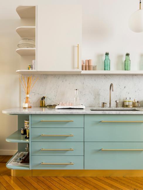 Salon z aneksem kuchennym z białą ścianą i turkusowymi szafkami