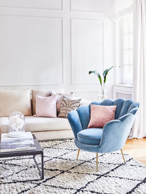 Jasny salon z bezową sofa, aksamitnym, niebieskim fotelem i stolikiem kawowym z marmuru