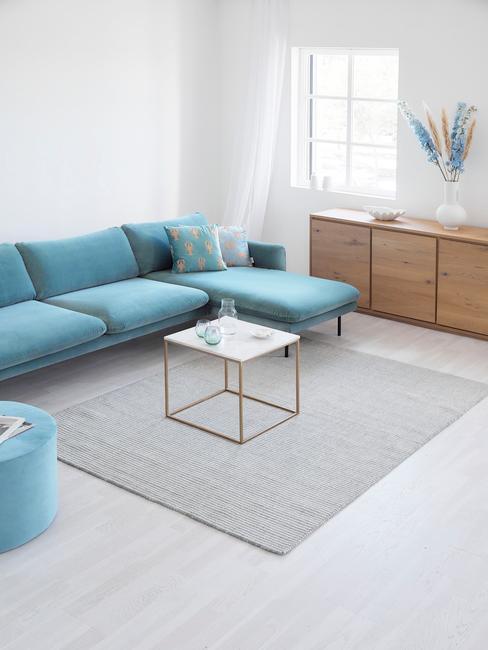 Jasny salon z trukusową, aksamitną sofa, marmurowym stolikiem oraz drewnianą komodą