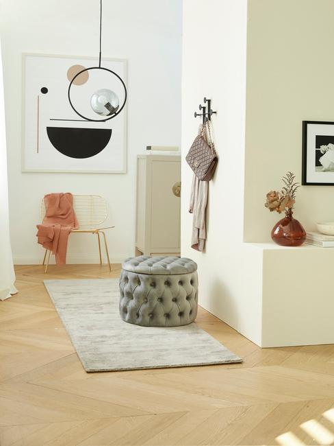 Biały korytarz z dekoracjami i aksamitnym pufem