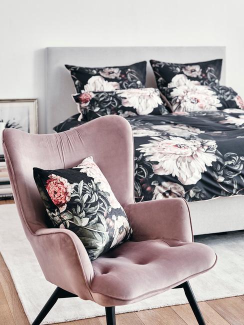Wnętrze białej sypialni z łożkiem i różowym fotelem i tekstyliami