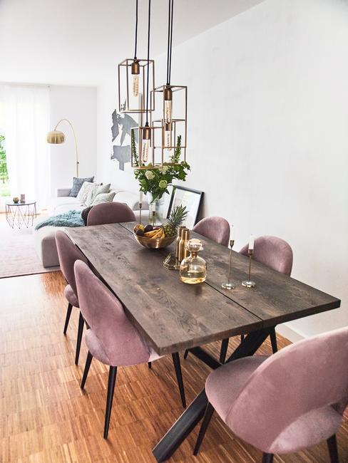 Jadalnia z dużym, drewnianym stołem oraz różowymi krzesłami z aksamitnym obiciem