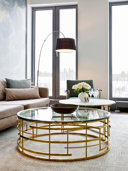 Salon w beżową sofą, lampą oraz szklanym stolikiem kawowym ze złotym stelażem