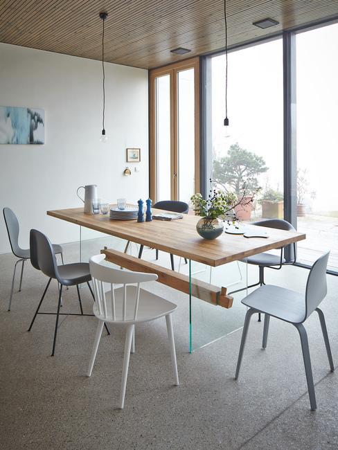 Jadalnia w stylu skandynawskimz dużym, drewnianym stołem i różnymi krzesłami w lofcie