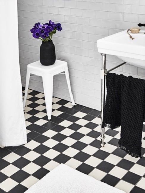 Close-up badkamer met zwart-witte tegels, lavabo en witte kruk met vaas bloemen