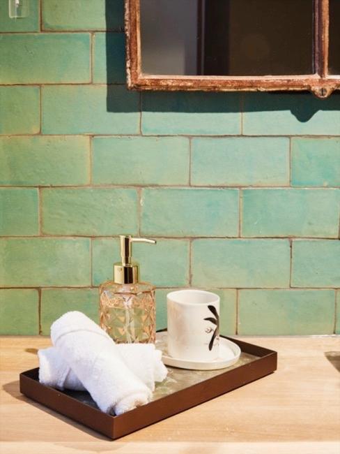 Close-up badkamer met wandtegels in turquoise en dienblad met handdoeken en decoratieve objecten