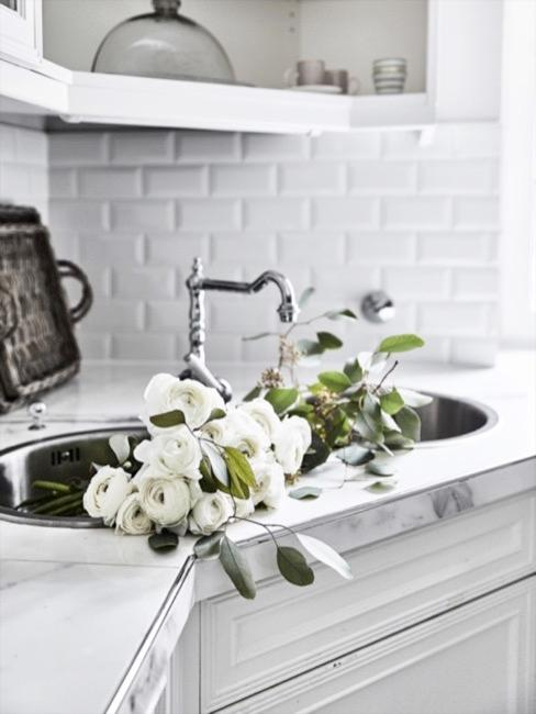 Witte keuken met witte wandtegels, kraan en witte bloemen