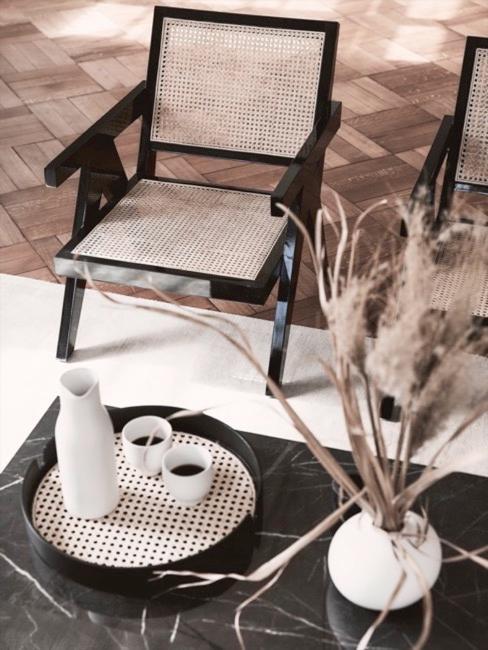 Plateau en cannage sur table basse en marbre noir et fauteuil lounge en cannage