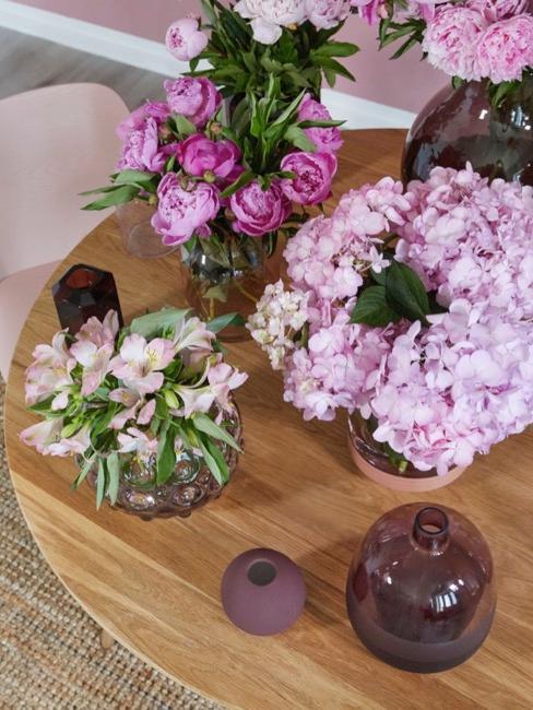 Lila bloemen in paarse vazen op houten tafel