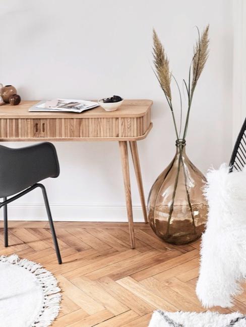 Bureau en bois clair avec fauteuil noir et grand vase en verre sur un parquet en bois ancien