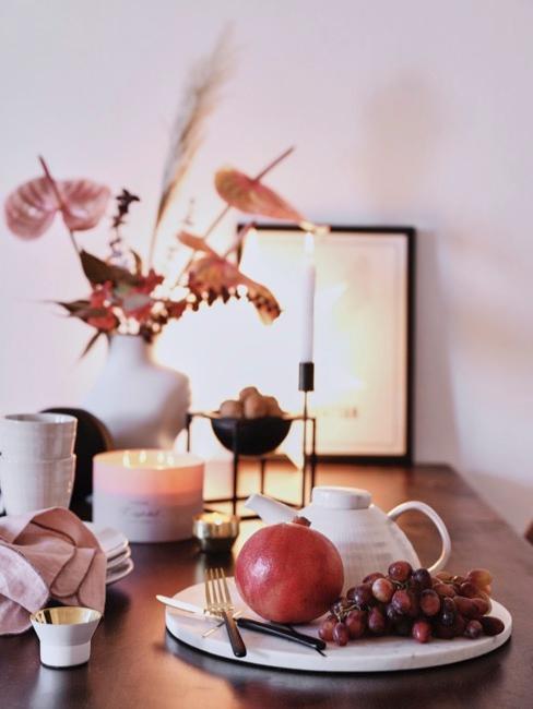 Decoración de mesa otoñal con plantas y frutas en tonos naranjas y vajilla blanca