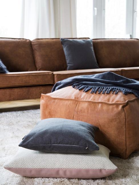 Salon avec un grand fauteuil et un pouf en cuir marron et des coussins sur le fauteuil ainsi que sur le tapis