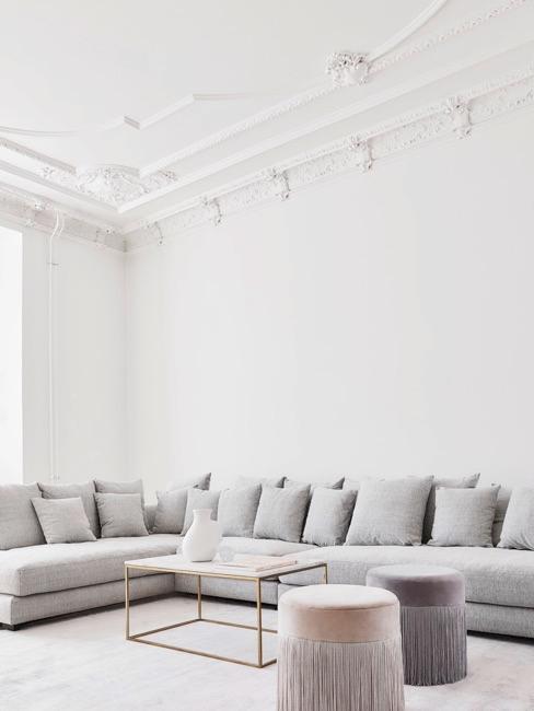 Jasny przestronny salon z szarą sofą, stolikiem kawowym i pufami