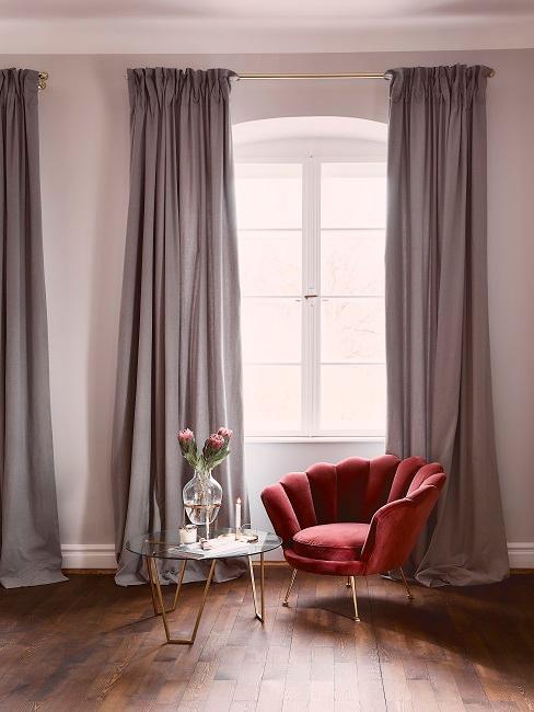 Aksamitne czerwony fotel w szarawym salonie