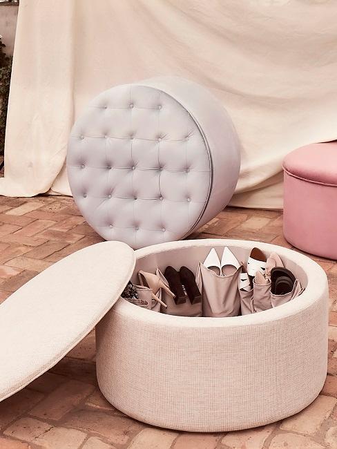 Puf w kolorze pudrowego różu ze schowek, w którym znajdują się różnorodne buty