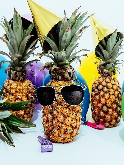 Ananas als Deko für die Hippie Party mit Sonnenbrillen und Partyhütchen