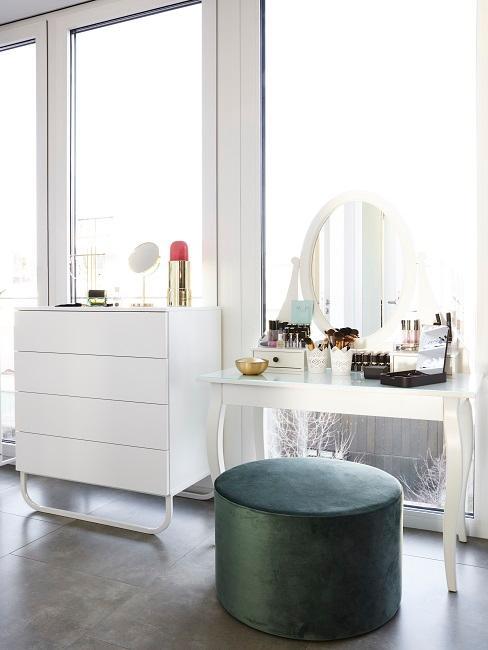 Biała toaletka z lustem w sypilani, stojąca obok komody oraz ciemnej pufy