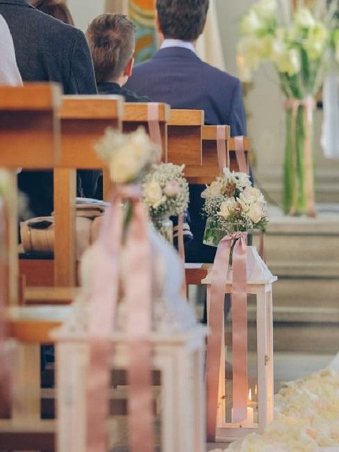 Ławki w kościele ozdobione kwiatami i wstążkami