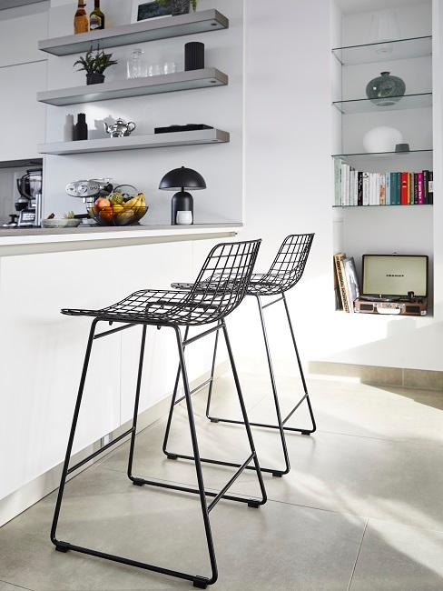 Offene Wohnküche in weiß mit schwarzen Stühlen
