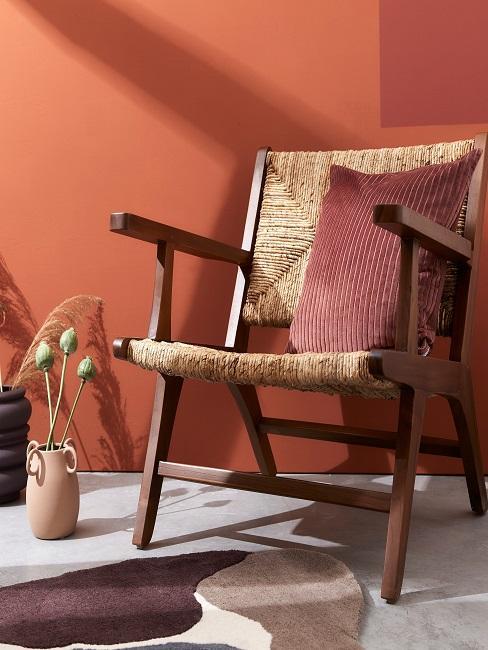 Terracotta farbenes Kissen auf Holzstuhl vor Terracotta farbenem Hintergrund