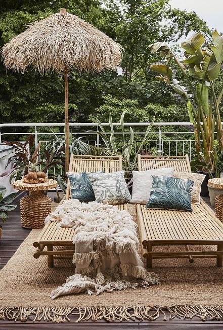 Zwei Sonnenliegen mit Kissen und Decke auf Balkon