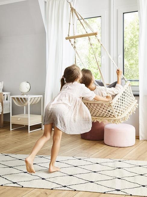 Kinder schaukeln in Hängesessel im Montessori Kinderzimmer