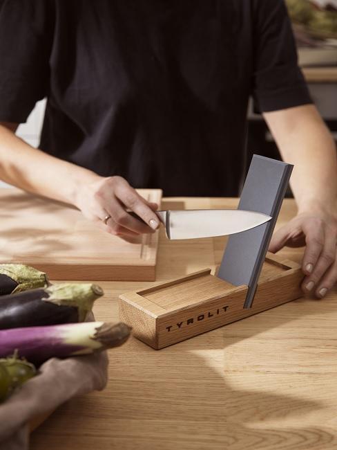 Person schärft Messer an Schleifstein