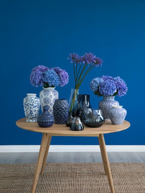 Mur bleu avec table en bois scandinave remplis de vases et de fleurs bleues