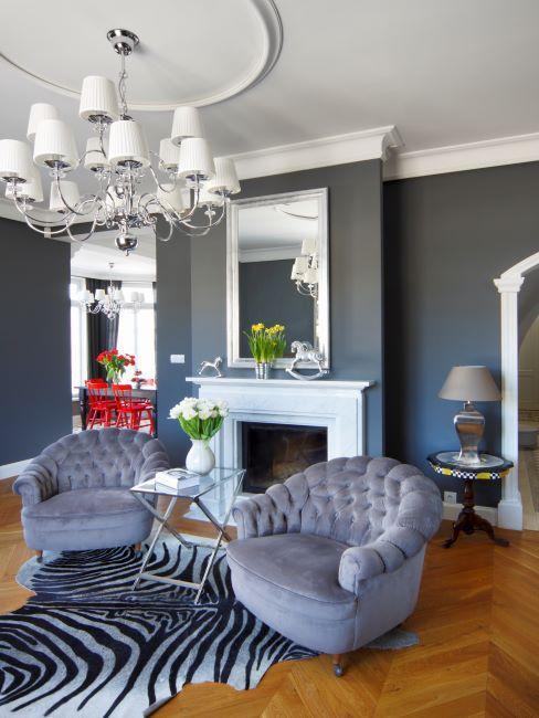 Salon élégant aux murs bleu-gris, fauteuils de la même couleur et beau parquet