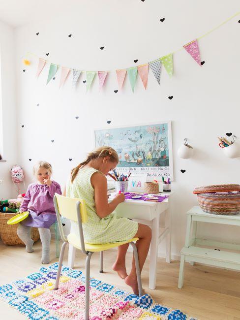 Grande fille assise au bureau en train de dessiner, petite fille assise à côté en train de jouer