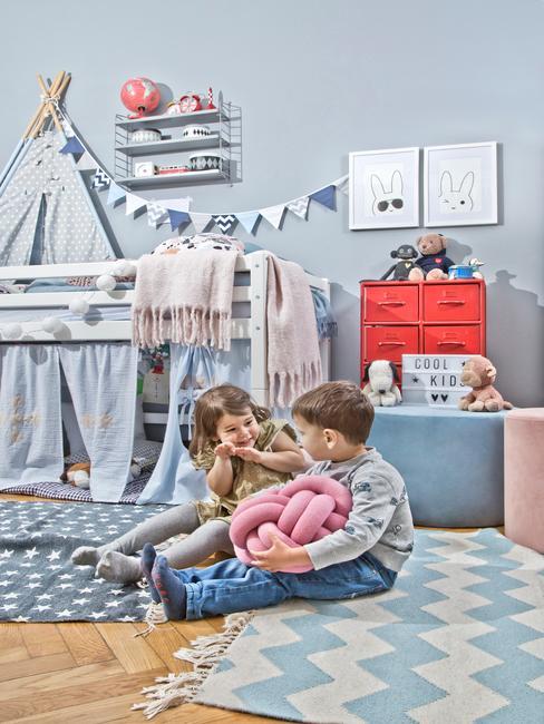 deux petits enfants qui rigolent ensemble dans une salle de jeux