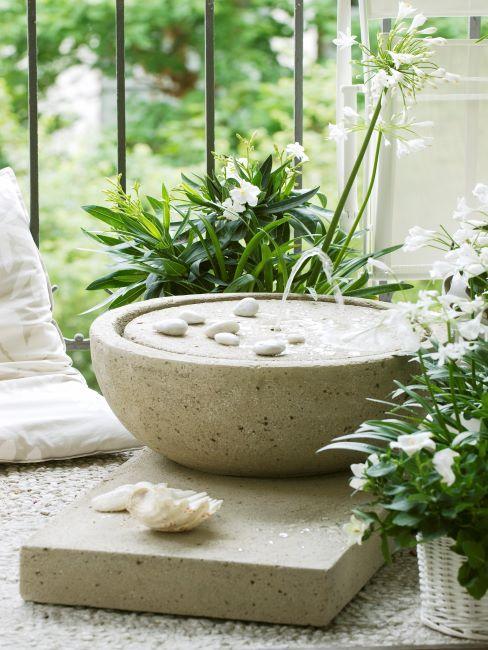 fontaine naturelle en pierre claire et plantes verte à fleurs blanches
