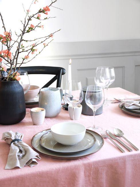Table dressée avec nappe rose, vaisselle en céramique et bouquet dans un vase