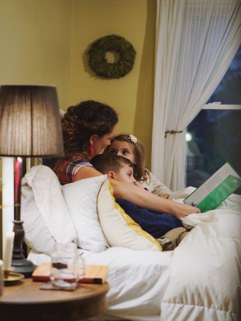 une mere en train de lire un livre a ses deux enfants, tous assis sur un canape blanc