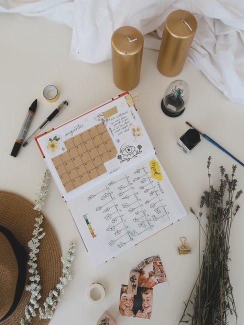 Open kalender met zelfgemaakte elementen en gouden kaarsen op een witte tafel