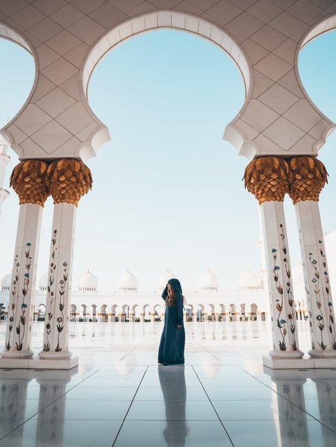 Vrouw tussen twee witte bogen in blauwe kleding