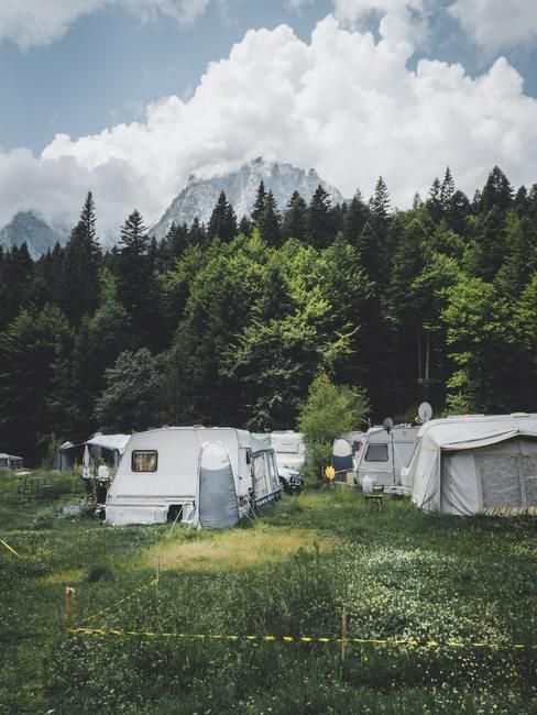 Camping met oude grijze tenten tussen de bergen en groene bomen