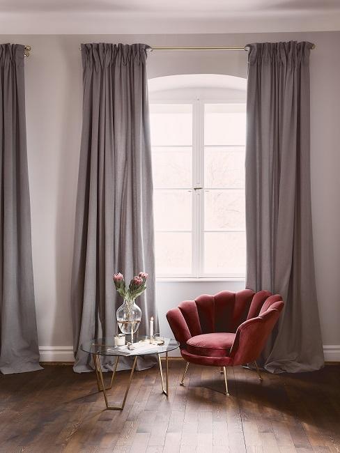 Bordeauxrode fauteuil met glazen bijzettafel en boeket in glazen vaas