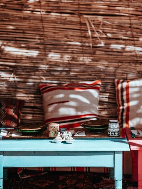 Roodachtige kussens op de bank naast de blauwe bijzettafel