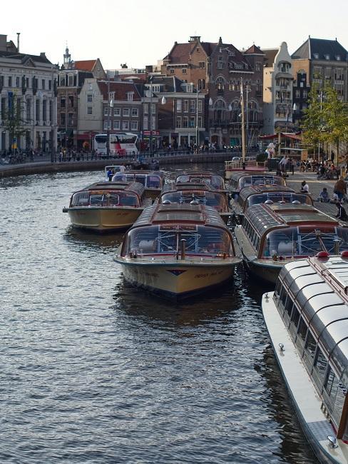 woonboten op de rivier met huizen in de achtergrond
