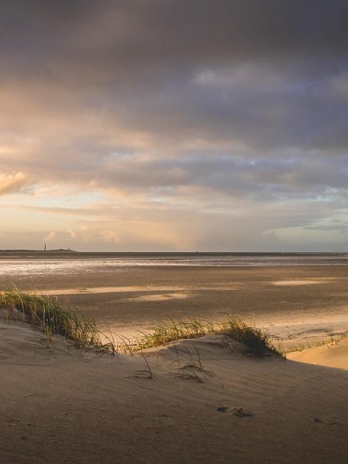 Duinen en strand bij zonsondergang