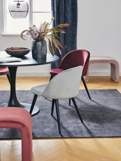 Fragment salonu z krzesłami, stolikiem na któym znajduje się wazon z proteą