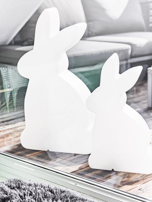 Dwie dekoracje w kształcie zajęczka wielkanocnego stojące na stole