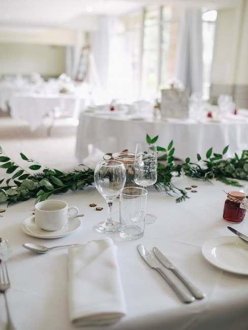 Główy stól weselny z zastawą oraz dwa okrągłe stoły weselne dla pozostałych gości