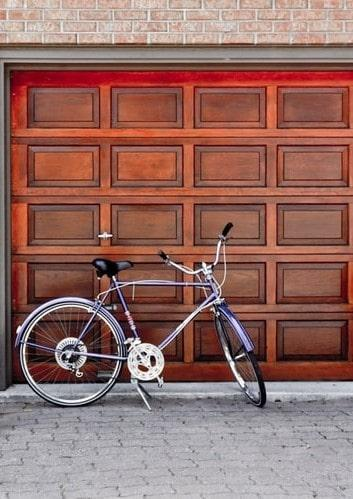 Rower stojący przed drewnianymi drzwami do garażu